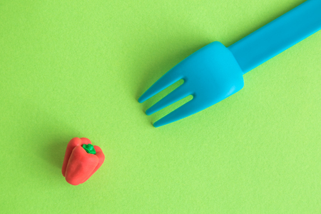 Flat lay of plastic fork and small rubber red pepper toy against green background minimal creative vegetarian concept.