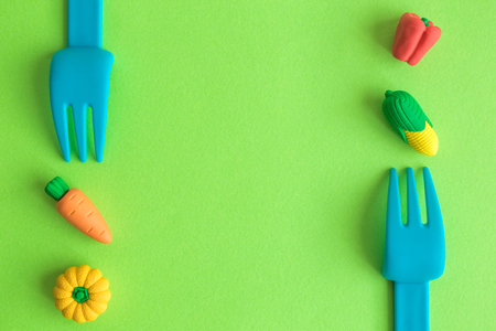 Flat lay of plastic forks with small rubber vegetable toys against green background minimal creative vegetarian concept.