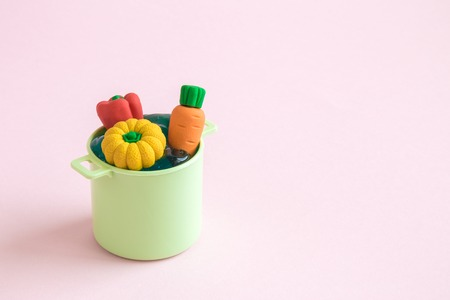Vegetables in pot toy minimal creative cooking concept. Space for copy. 版權商用圖片
