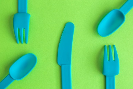 Flat lay of plastic tableware on green background, minimal food creative concept.