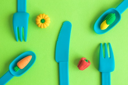 Flat lay of plastic tableware with vegetable toys on green background, minimal food creative concept.