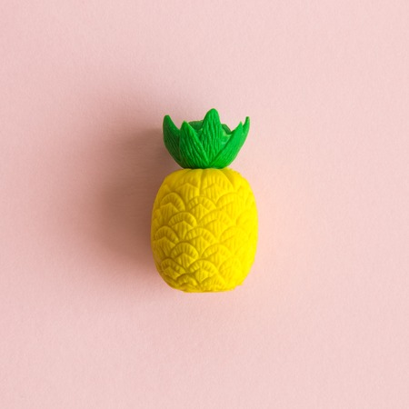 Flat lay of pineapple fruit toy on pastel pink background minimal creative concept.