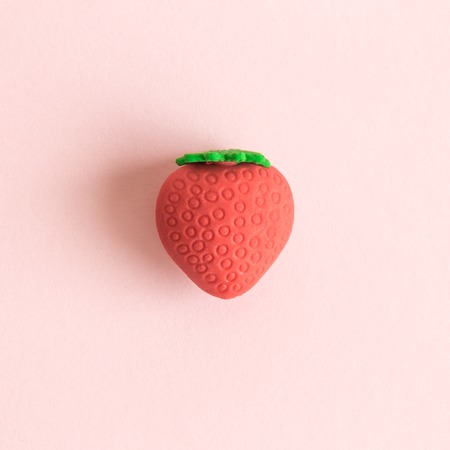 Flat lay of strawberry fruit toy on pastel pink background minimal creative concept.