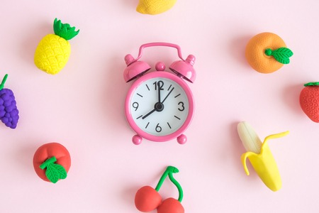 Flat lay of alarm clock and rubber fruit models on pastel pink background minimal creative concept.
