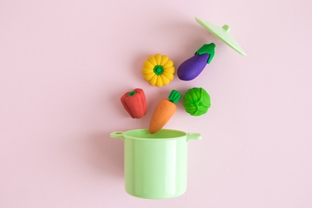 Flat lay of vegetable model toys falling into pot on pastel pink background minimal creative concept.