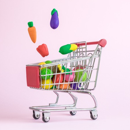 Carrot, eggplant,pepper and corn falling into shopping cart with fruits and vegetables abstract isolated on rose.