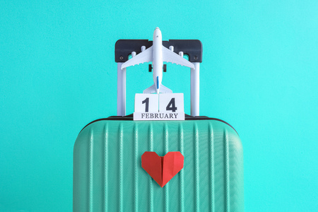 Suitcase with 14 of february wooden calendar and airplane model toy with origami red heart on light blue background minimal creative travel concept.