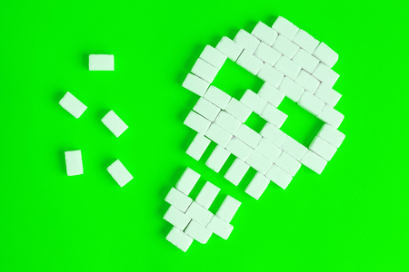 Flat lay of skull made of sugar cubes on green background unhealthy food minimal creative concept. Stock Photo