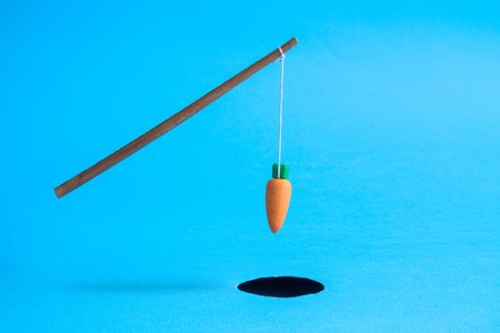 Stick with carrot above rabbit hole on pastel blue background minimal creative concept. Stock Photo