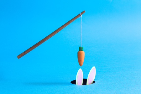 Stick with carrot above rabbit hole with bunny ears on pastel blue background minimal creative concept.