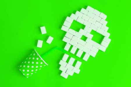 Skull made of sugar cubes drinking unhealthy drink against green background minimal creative concept.