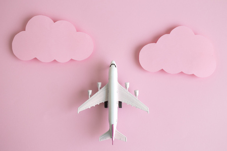 Flat lay of airplane model with pastel pink clouds minimal creative travel concept. Фото со стока