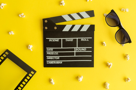 Flat lay of clapper board and glasses with film strip frame and popcorn isolated on yellow.