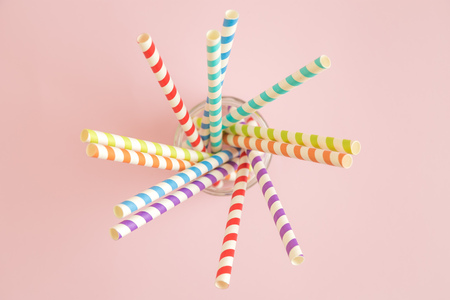 Colorful drinking straws against pastel pink background minimal creative concept. Imagens