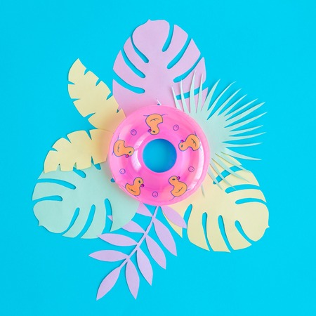 Creative background made of swimming float and tropical leaves made of paper against pastel pink background minimal summer and travel concept. 版權商用圖片