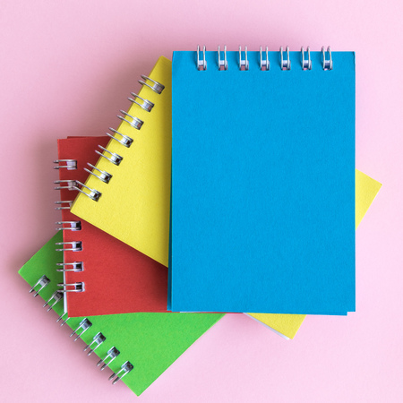 Close up of colorful notebooks on pastel pink background minimal creative concept. Space for copy. Foto de archivo - 118588697
