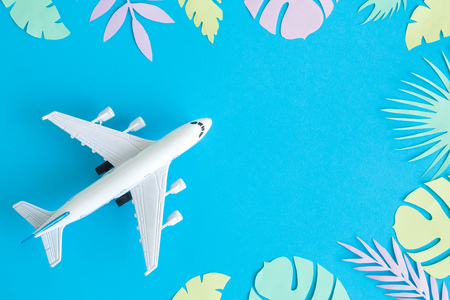 Flat lay of airplane model toy with colorful tropical leaves made of paper minimal travel and summer vacation concepts.