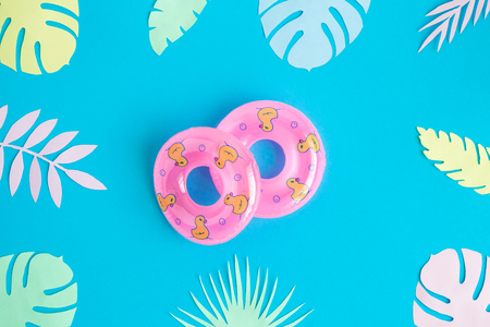 Flat lay of swimming floats and colorful tropical leaves against blue background minimal creative summer and travel concepts. 版權商用圖片
