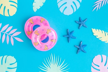 Flat lay of swimming floats with sea stars and colorful tropical leaves against blue background minimal creative summer and travel concepts.