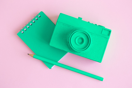 Flat lay of retro camera and notebook with pencil on pastel pink background minimal creative concept.