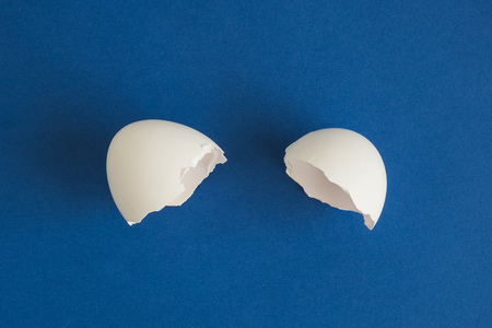 Flat lay of egg shell against dark blue background minimal creative concept.