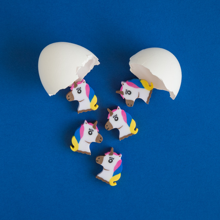 Flat lay of unicorns hatching from egg shell minimal creative concept.