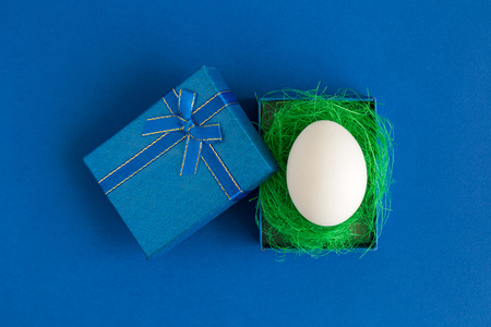 Flat lay of white egg in gift box minimal creative easter concept.