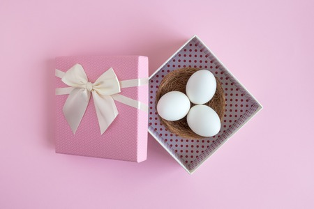 Flat lay of white eggs in pastel pink gift box minimal creative easter concept.