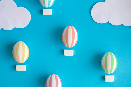 Hot air balloons made of easter eggs and sugar cubes with paper clouds minimal creative holiday concept. Foto de archivo - 118613372