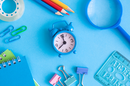 Small alarm clock with school supplies on blue background minimal creative back to school concept. Foto de archivo - 118613374