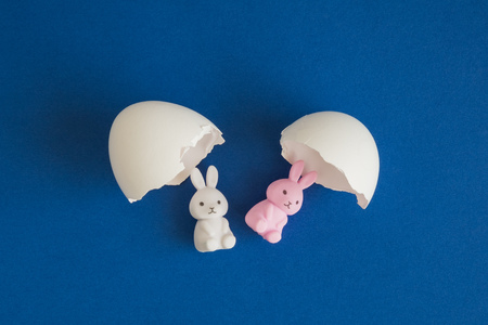 Flat lay of bunnies hatching from egg shell minimal easter creative concept. 版權商用圖片
