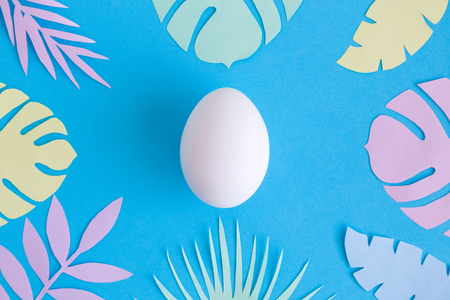 Flat lay of white egg and colorful tropical leaves on blue background minimal creative concept.