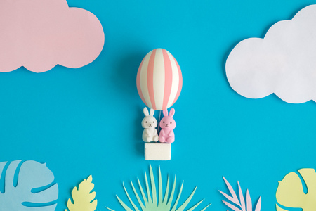 Rabbits in easter egg hot air balloon with colorful tropical leaves minimal creative holiday concept.