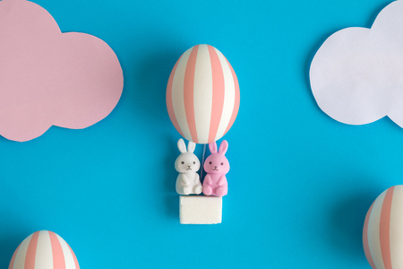 Rabbits in easter egg hot air balloon minimal creative holiday concept.