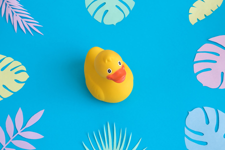 Rubber duck with colorful tropical leaves against pastel blue background minimal creative summer concept. Foto de archivo - 118613474