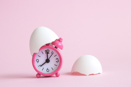 Egg shells and small alarm clock on pastel pink background minimal easter time creative concept. Space for copy.