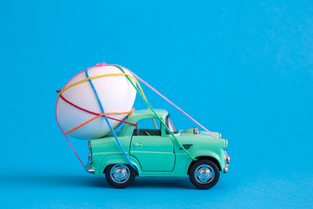 Car toy carrying easter egg tied with colorful thread minimal creative holiday and travel concepts.