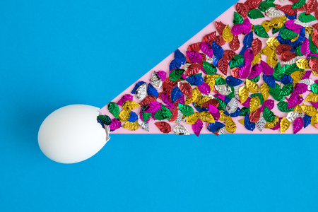 Egg shell with colorful leaves on blue background minimal easter and spring creative concept. Foto de archivo - 119040136