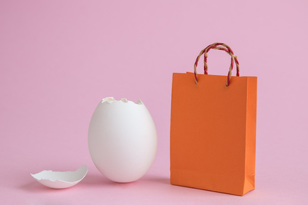 Egg shell and shopping bag against pastel pink background minimal easter creative concept.