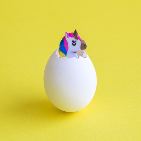 Unicorn hatching from egg against yellow background minimal easter creative concept.