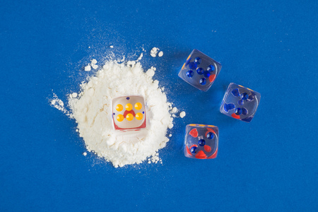 Flat lay composition of cocaine and dices against blue background minimal creative concept.