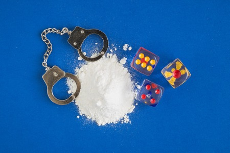 Flat lay composition of cocaine with handcuffs and dices against blue background minimal creative concept. Foto de archivo - 119040761