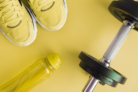 Flat lay of bottle of water, sneakers and dumbbells on yellow background minimal fitness creative concept.