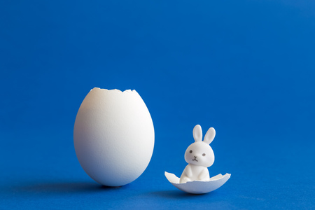 Bunny sitting on egg shell against blue background minimal creative easter concept. Foto de archivo - 119040767