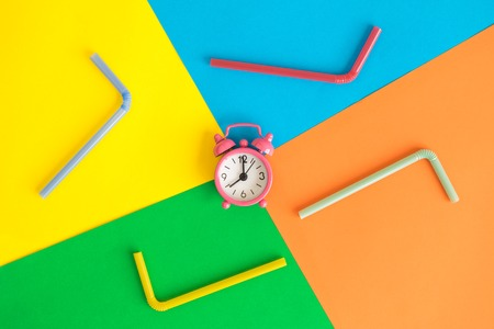 Flat lay of small pink alarm clock and drinking straws against colorful background minimal creative drink concept.