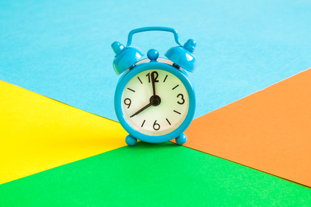 Alarm clock on multicolored background minimal creative concept.
