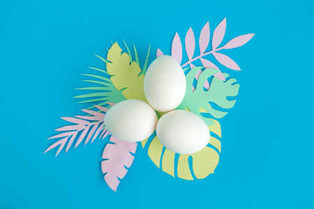 Flat lay of white eggs and colorful tropical leaves on blue background minimal creative concept.