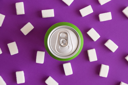 Flat lay of aluminum can with sugar cubes on purple background minimal creative unhealthy food creative concept.