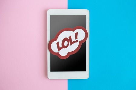 Flat lay of digital tablet device or mobile phone with lol text in speech bubble against pastel background minimal technology creative concept. Reklamní fotografie