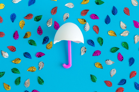 Flat lay of umbrella made of egg shell and drinking straw with rainbow colored leaves against blue background minimal creative concept. Reklamní fotografie